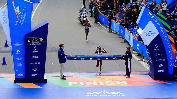 Photo of New York City Marathon finish line with winner about to break through the tape.