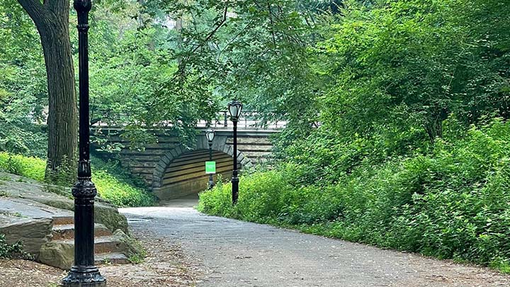 Photo of pedestrian pathway leading under arch below roadway in Central Park, New York, NY.
